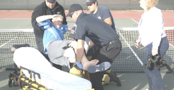 BENICIA HIGH senior Tyler Lorz gets lifted into a stretcher by a medical team after dislocating his knee Thursday against American Canyon as his mother, Marya, looks on.