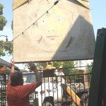 PHIL JOY'S MOVERS hoist a piece of concrete, a piece of First Street sidewalk removed for tree root repair, onto a giant easel to display the work of chalk artist Stan Golovich.  Joy Alberts photo