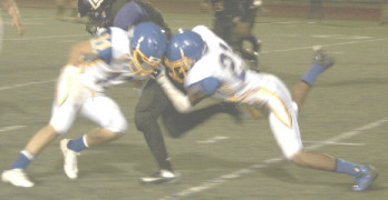 BENICIA DEFENDERS Kyle Hanson-Regalado (left) and DeMarea Jackson wrap up Armijo running back Daerion Spencer.