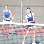 BENICIA'S MADISON LAMMERT returns a shot as doubles teammate Adeline Morley backs up the play against Fairfield.