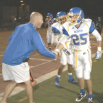 ALEX OSTERHOLT (25) gets congratulated by head coach Craig Holden after running for a 44-yard touchdown against Vallejo on Friday.