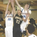 BENICIA'S Jack MacDowell (32) and Brandon Barrett (24) squeeze Concord's Dru Solis for a loose ball.