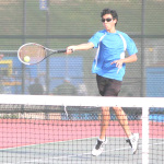 AIDAN MCANINCH of Benicia rips a forehand volley at his Vallejo opponent.