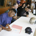 MARQUIS PERRILLIAT (left) and St. Patrick-St. Vincent High teammate Chris Stinchcomb (right) sign letters of intent to play football for Linfield College in Oregon.