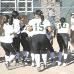 JAYDEE BOURSAW (far right) gets greeted at home plate by her Lady Bruin teammates after clubbing a home run against Pinole Valley.