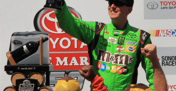 KYLE BUSCH raises a class of wine in the winner's circle Sunday at Sonoma Raceway. Keri Luiz/Staff