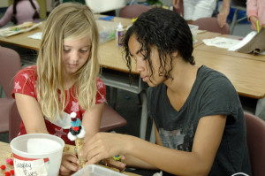 Isabel Del Rio (Left) works with teen volunteer Breanna Christian on a project at a previous EcoArt Camp. (Photo by Peg Jackson)